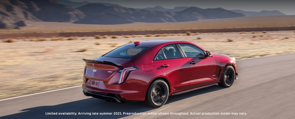 Back side view of the 2022 Cadillac CT4-V Blackwing driving on the road.