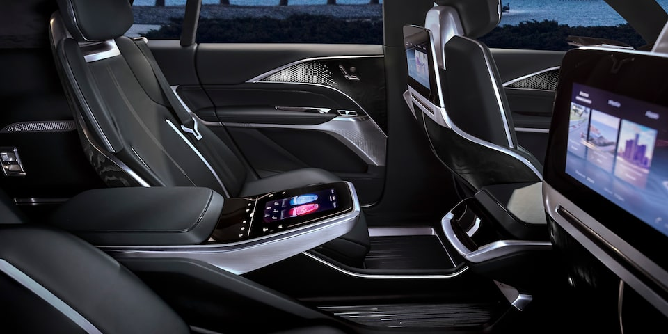 Cadillac LYRIQ luxury electric SUV interior passenger seats featuring center control and headrest monitors.